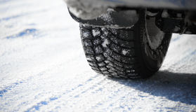 Close-up Image of Winter Car Tire on Snowy Road. Drive Safe Concept Royalty Free Stock Photo