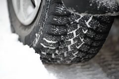 Close-up Image of Winter Car Tire on Snowy Road. Drive Safe Concept Royalty Free Stock Images