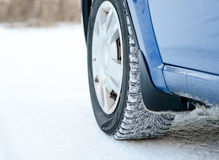 Close-up Image of Winter Car Tire on Snowy Road. Drive Safe Concept. Stock Photo
