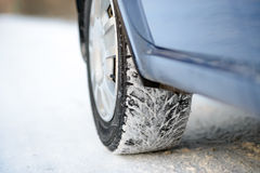 Close-up Image of Winter Car Tire on Snowy Road. Drive Safe Concept. Stock Photos