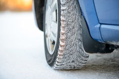 Close-up Image of Winter Car Wheel on Snowy Road. Drive Safe Concept. Stock Photo
