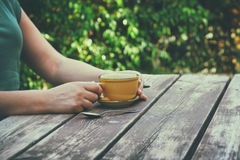 Close up image of woman drinking coffee outdoors, next to wooden table at afternoon. filtered image. selective focus stock photo