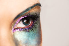 Close up of image of woman's turquoise eye with colorful rainbow makeup Stock Photos