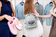 Close-up image of women holding new shoes and backpack showing their purchase to camera with apparel on hangers in. Background royalty free stock photography
