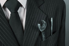 Close-up image of wrench in a pocket of suit businessman Stock Images