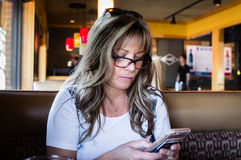 Close up image of young ash blonde woman on her cell phone. Horizontal close up image of a caucasian woman wearing glasses sitting in a restaurant and checking Royalty Free Stock Photo