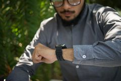 Close up image of young man looking at his smartwatch. Close up image of young man looking at his smartwatch background stock photos