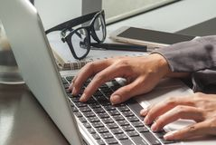 Close-up image of a young woman who is typing on a laptop stock image