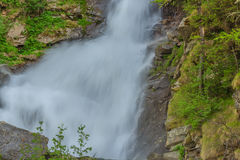 Close-up of an impetuous jump of a waterfall in the midst of mountain vegetation. An imposing waterfall falls impetuous from the glaciers in the National Park of Stock Photography