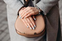 Perfect blue manicure and cared hands. Close up of incognito young woman holding hands with perfect blue manicure on beige leather bag and gray coat. Woman stock photography