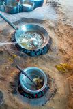 Close up of Indian food inside of a metallic trays in the ground, using coal to cook in kitchen in Jaipur, India.  Royalty Free Stock Images