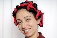 Close-up of Indian girl with curlers in her hairs. Royalty Free Stock Images