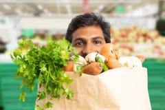 Close-up of supermarket employee hiding behind grocery bag. Close-up of indian male supermarket or hypermarket employee hiding behind grocery paper bag stock photos