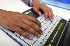 Close up of Indian mans hands typing on laptop Stock Image