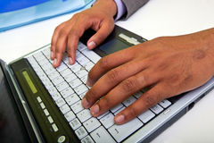Close up of Indian mans hands typing on laptop Stock Images
