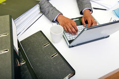Close up of Indian mans hands typing on laptop with folders and mug Royalty Free Stock Photography