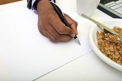 Close up of Indian mans hands writing on paper next to cereal Royalty Free Stock Photography