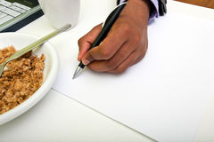 Close up of Indian mans hands writing on paper next to cereal Royalty Free Stock Photos