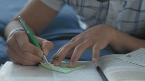 Close-up, Indian student in glasses makes records in a crib lying on a bed. Close-up, Indian student in glasses makes records in a cheat sheet on a bed in a dorm stock footage