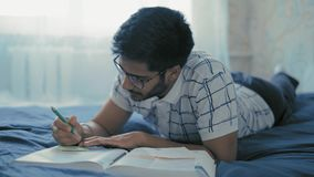 Close-up, Indian Student in Glasses Prepares for a Recline on a Bed in a Dorm Room. Close-up, Indian Student in Glasses Prepares for Examinations, Writes a Cheat stock footage