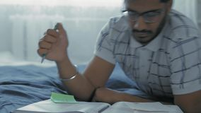 Close-up, Indian Student in Glasses Teaches Lessons, Lying on a Bed in a Dorm Room. Close-Up, Indian Student in Glasses Teaches Lessons, Writes Entries in the stock video footage