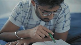 Close-Up, Indian Student in Glasses Thoughtfully Reads Entries in the Lay Lie on the Bed. Close-Up, Indian Student in Glasses Thoughtfully Reads Entries in Lay stock video