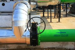 Close up of a industrial cold air and hot air pipe. With a black valve Industrial pilot plant of heat pipe. green cold water pipe and metallic hot water pipe royalty free stock image