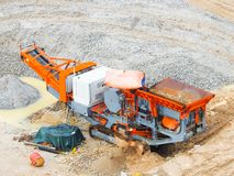 Close up of industrial mechanical conveyor belt or rock crusher working on construction site. Selective focus and crop fragment royalty free stock photography