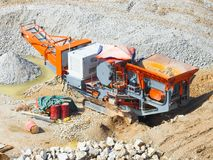 Close up of industrial mechanical conveyor belt or rock crusher working on construction site. Selective focus and crop fragment royalty free stock images