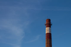 Close up of industrial pipe on blue sky background, factory emissions as ambient air pollution. Stock Image