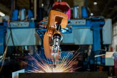 Close-up industrial robot is welding in a car factory. Close-up industrial robot is welding metal part in a car factory stock photography