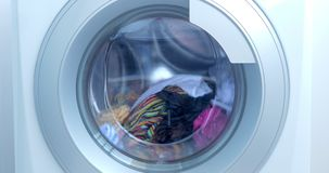 Close Up Industrial Washing Machine Washes Colored Clothing and White Linen, White Striped Clothing. Cylinder Spinning