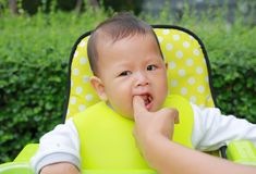 Close-up infant baby boy sitting on kid chair eating with something stuck in his mouth and mother help to keep out.  stock photo