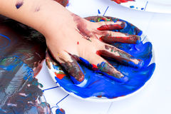 Close up of infant hand soaked in blue paint. Royalty Free Stock Image
