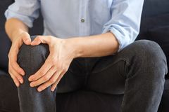 Close up of inflamed knee , man suffering leg pain. Leg and knee pain concept , man sitting on the couch stock image