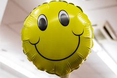 Close up of inflated yellow smiling face balloon Royalty Free Stock Photo