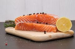 Ingredients. Salmon filet surrounded by lemon, spices and herbs on a wooden board. stock images
