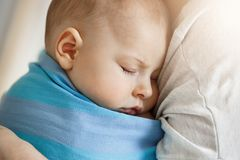 Close up portrait of innocent little child, sleeping on mother hands in blue baby sling. Quite and relaxing scene Royalty Free Stock Photos