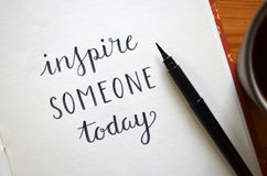 `INSPIRE SOMEONE TODAY` brush calligraphy in notebook. Close-up of `INSPIRE SOMEONE TODAY` inspirational quote hand-lettered in notebook with brush calligraphy Royalty Free Stock Photography
