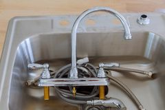 Installing a stainless steel kitchen sink. Close-up Of installing a stainless steel kitchen sink royalty free stock images