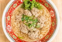 Close up of Instant noodle with meat ball and green Coriander on wood table. Close up of Instant noodle with meat ball and green Coriander stock photo