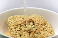 Close up instant noodle soup flavor. In the cup is pouring boiling water Royalty Free Stock Photo