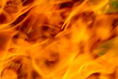 A close up of intense red flames in a fire. Fire, red and orange texture on a black background. blurry.  Stock Photo