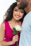 Close up of interracial couple holding white rose. Stock Image