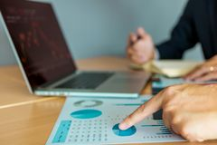 Close up investor hand points to the company operating results for analysis of stock purchases.  royalty free stock photos