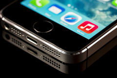 Apple iphone 5 s. Close up of a Black apple iphone 5 s on a black reflective surface Stock Photography