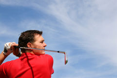 Close up of Iron. Young golfer hitting an iron against a half cloudy sky Stock Photos