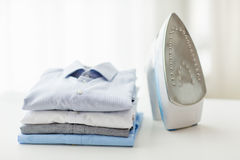 Close up of iron and clothes on table at home Royalty Free Stock Photos