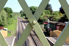 Close up of the ironwork of an old railway footbridge, with track, platform, signals and rolling stock in the blurred. Background, on a sunny summer day royalty free stock images