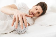Close up of an irritated young man. Turning alarm off in the morning while lying in bed Royalty Free Stock Photography